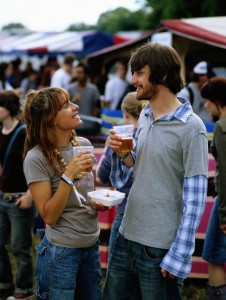 Young couple at festival holding plastic beer glasses, smiling